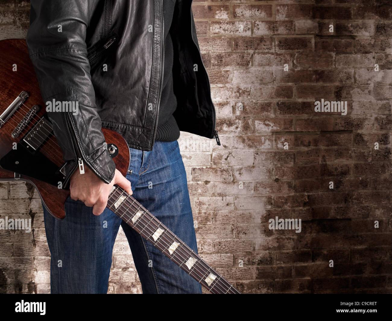 mann in einer lederjacke stehen vor der mauer und holding e gitarre musik konzert. Black Bedroom Furniture Sets. Home Design Ideas