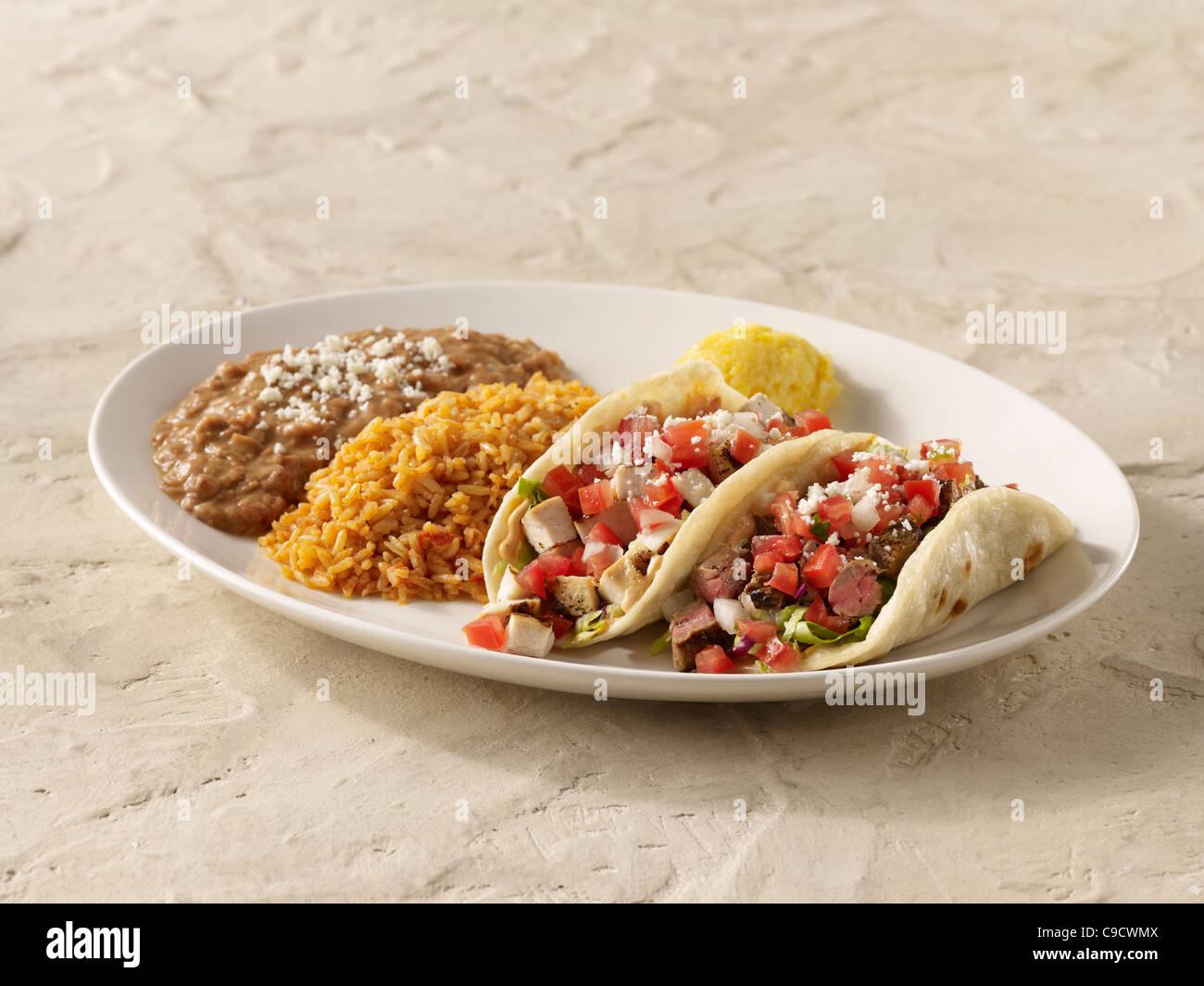 Eine Fajita Chicken Taco und Steak Taco-Combo mit Salsa Fresca und Käse garniert, serviert mit spanischen Reis Stockbild