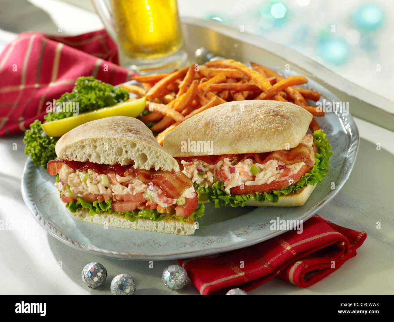 Ein Gourmet-Handwerker-Hummer-Club-Sandwich mit Speck, Salat und Tomaten serviert mit Pommes Frites und ein Bier Stockbild
