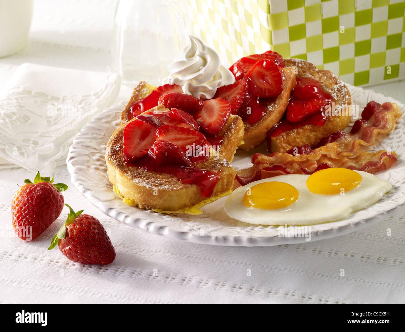 Erdbeer-French-Toast mit Speck und Eiern Stockbild
