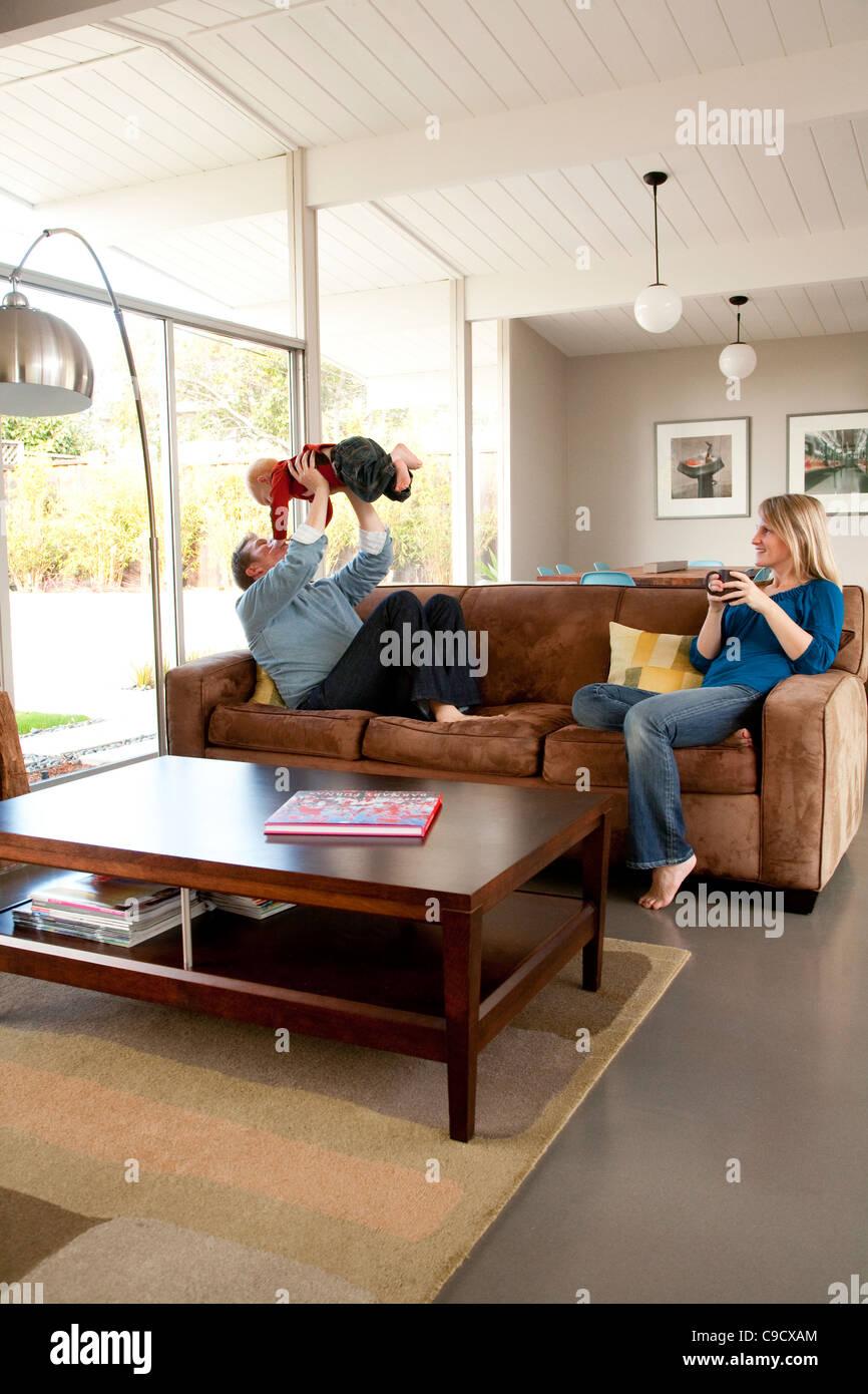 Vater, Mutter und Sohn im Wohnzimmer Stockbild
