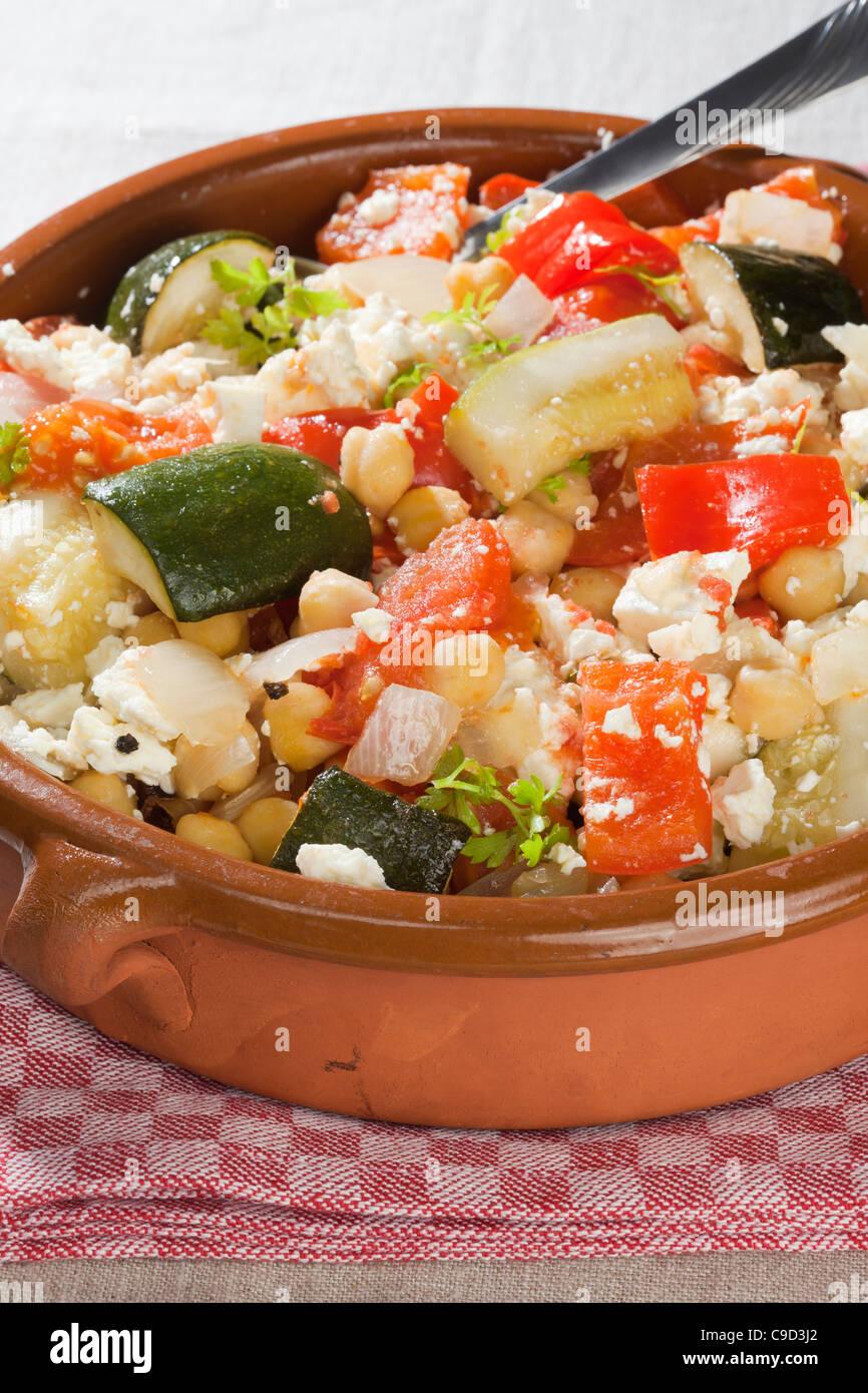 Warmer Salat mit Zwiebeln, Tomaten, Paprika, Zucchini, Ziegenkäse, Kichererbsen, Petersilie, Olivenöl, Stockbild