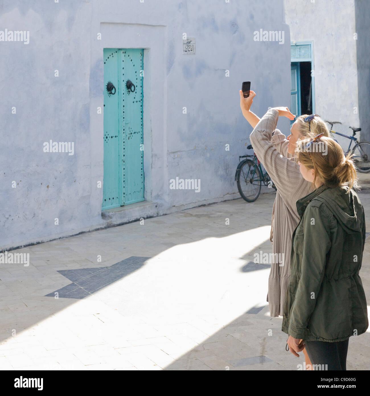 Tunesien, Kairouan, Mutter und Tochter unter Bild mit Handy Stockbild
