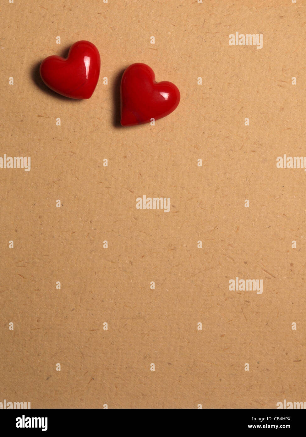 2 Herzen auf grobem Papierhintergrund Stockbild