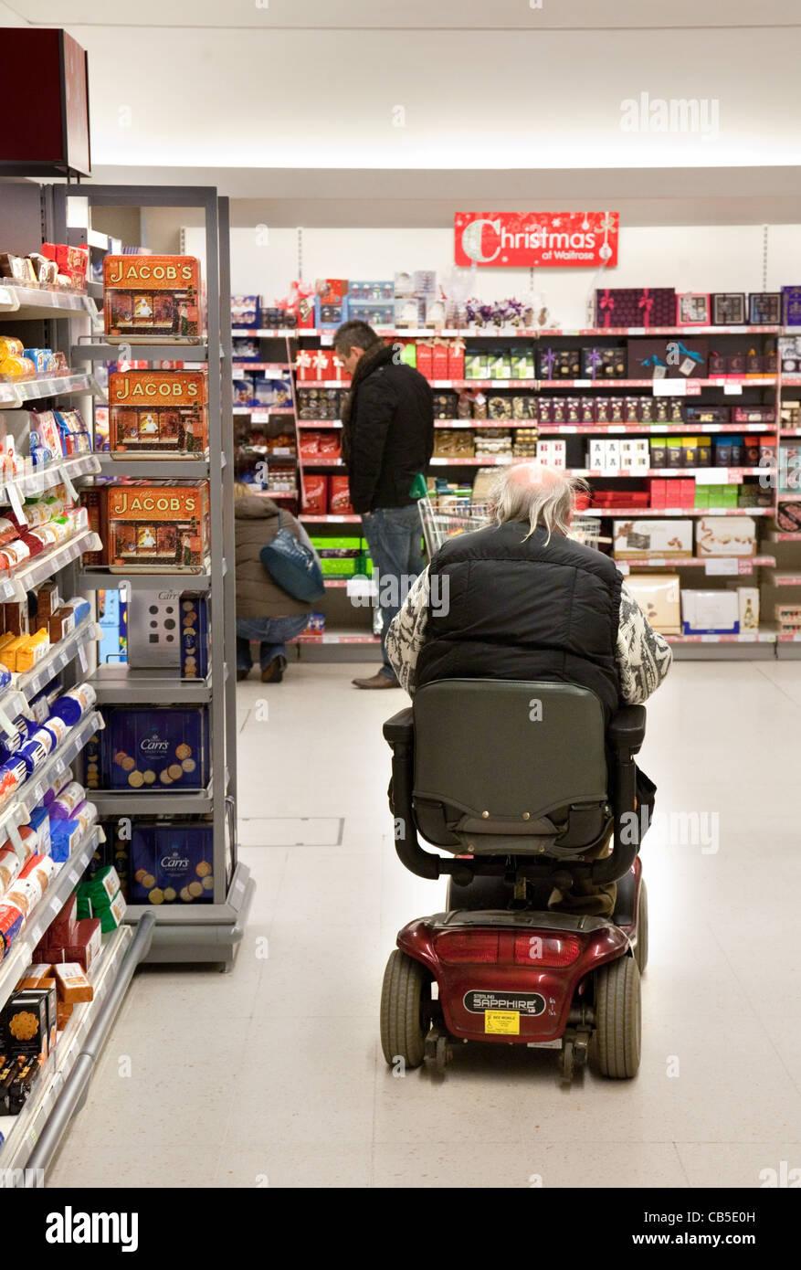 Behinderte Menschen shopping auf seine Behinderung scooter in einem Supermarkt Waitrose, Großbritannien Stockbild
