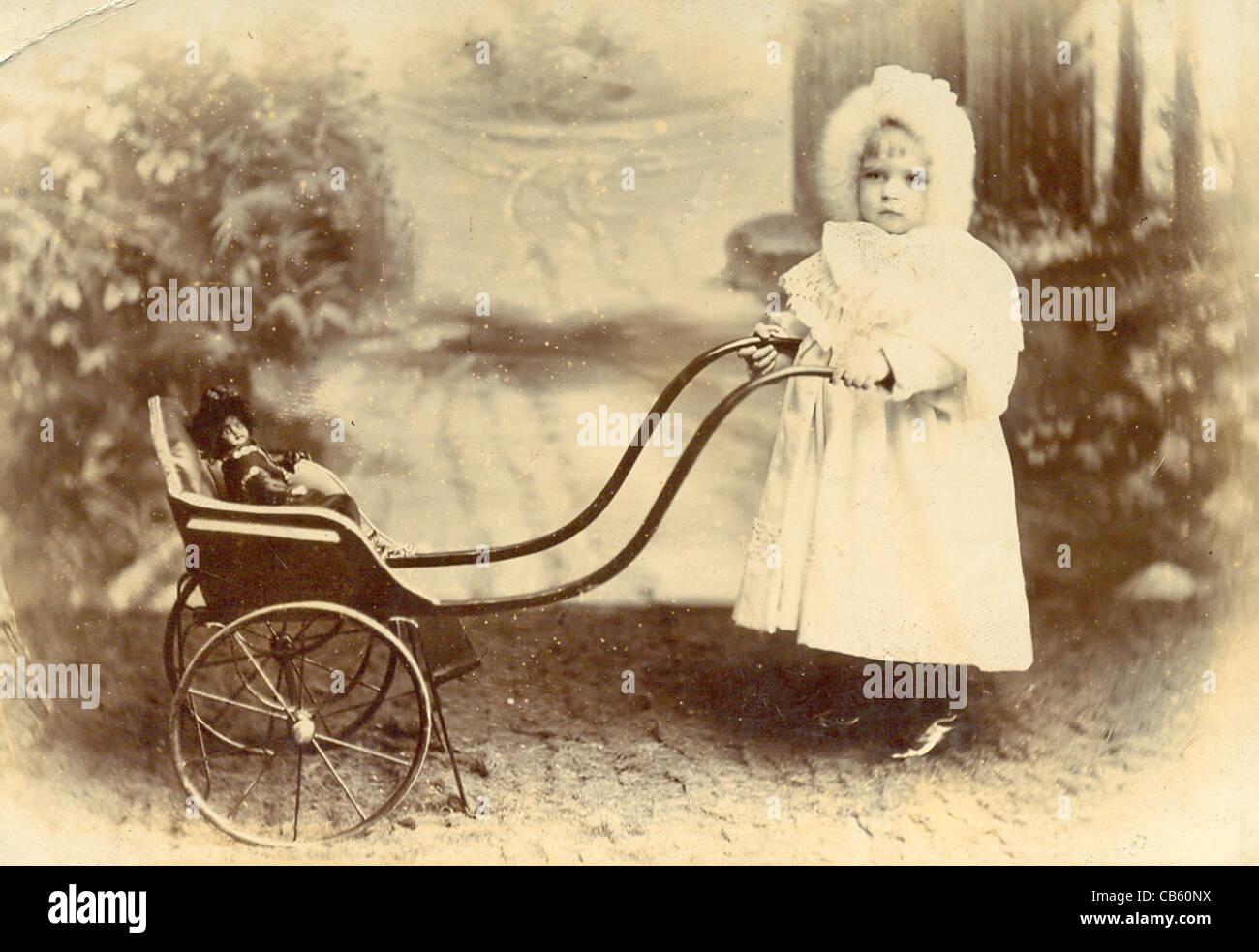 Kabinett Foto von Kleinkind mit Kinderwagen und Puppe Stockbild