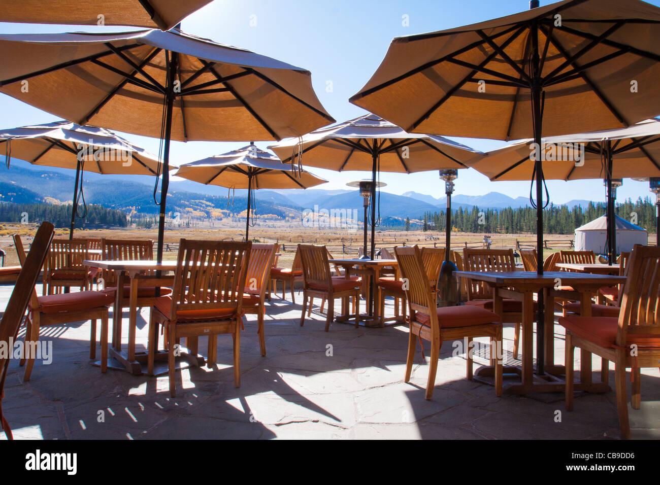Schirme über Terrasse Essbereich in einem Mountain Resort Lodge mit malerischen Blick auf die Bergkette in Stockbild