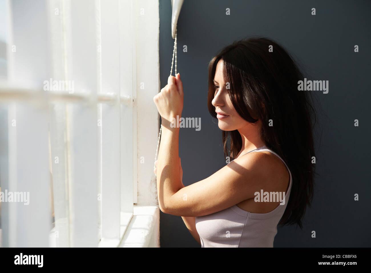 Lächelnde Frau, die Erhöhung der Jalousien Stockbild