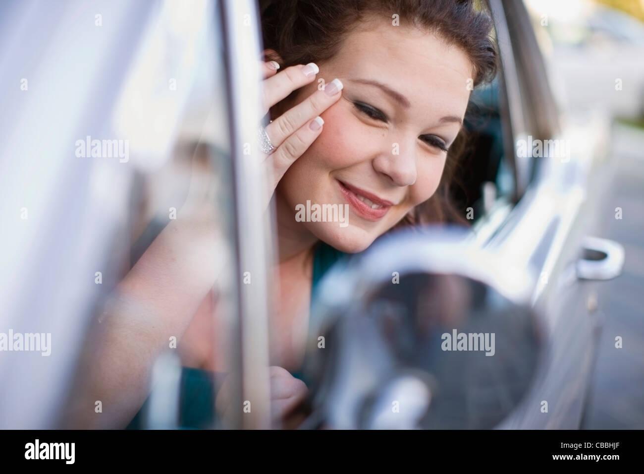 Teenager-Mädchen Make-up im Auto prüfen Stockbild