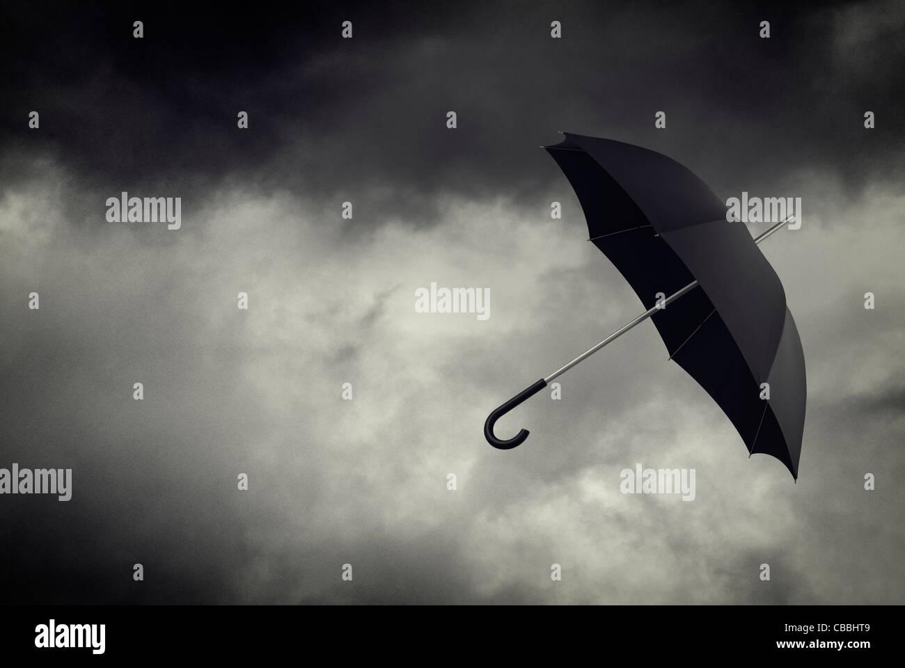 Regenschirm im stürmischen Himmel schweben Stockbild
