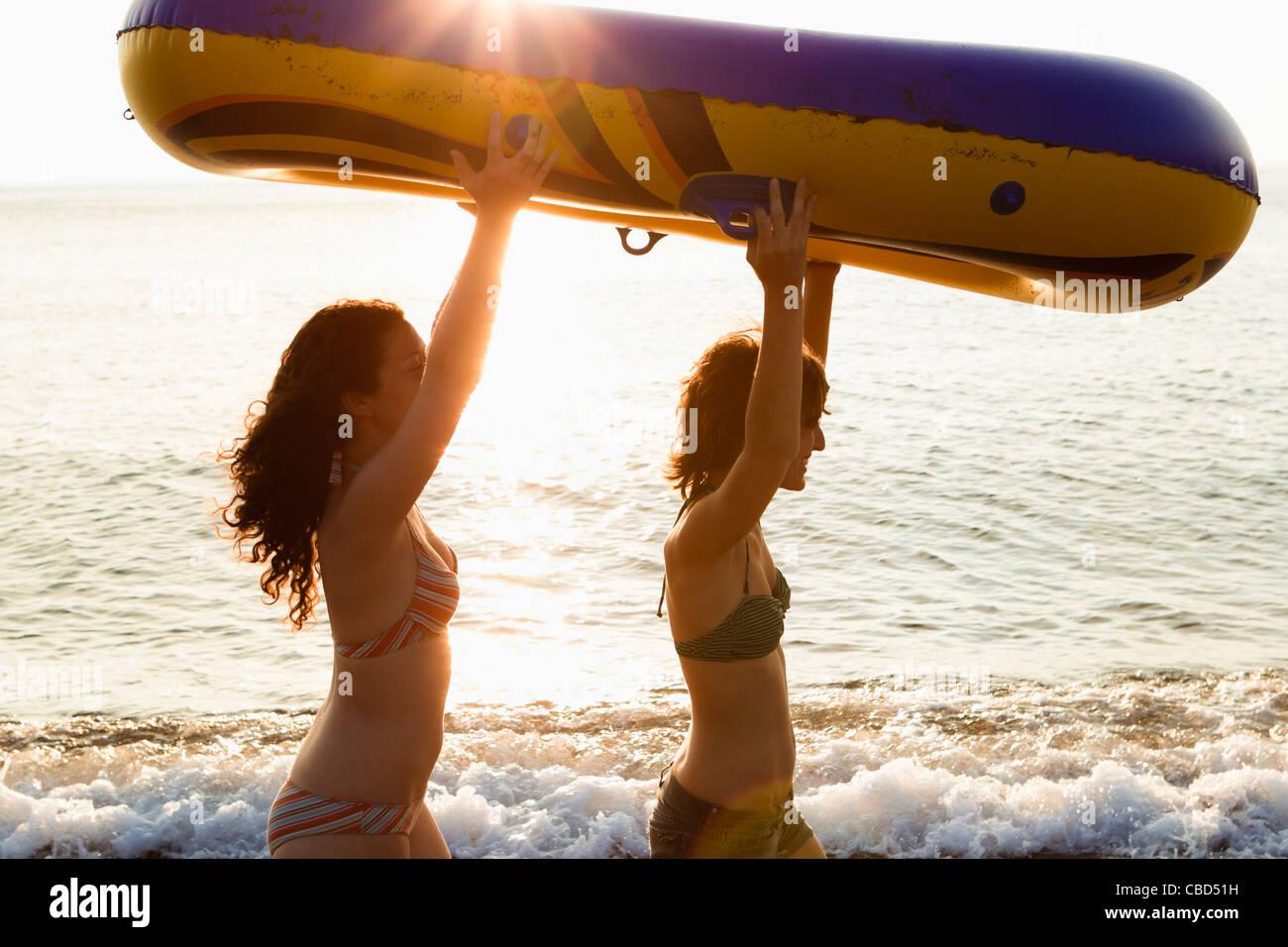 Frauen tragen Schlauchboot am Strand Stockbild