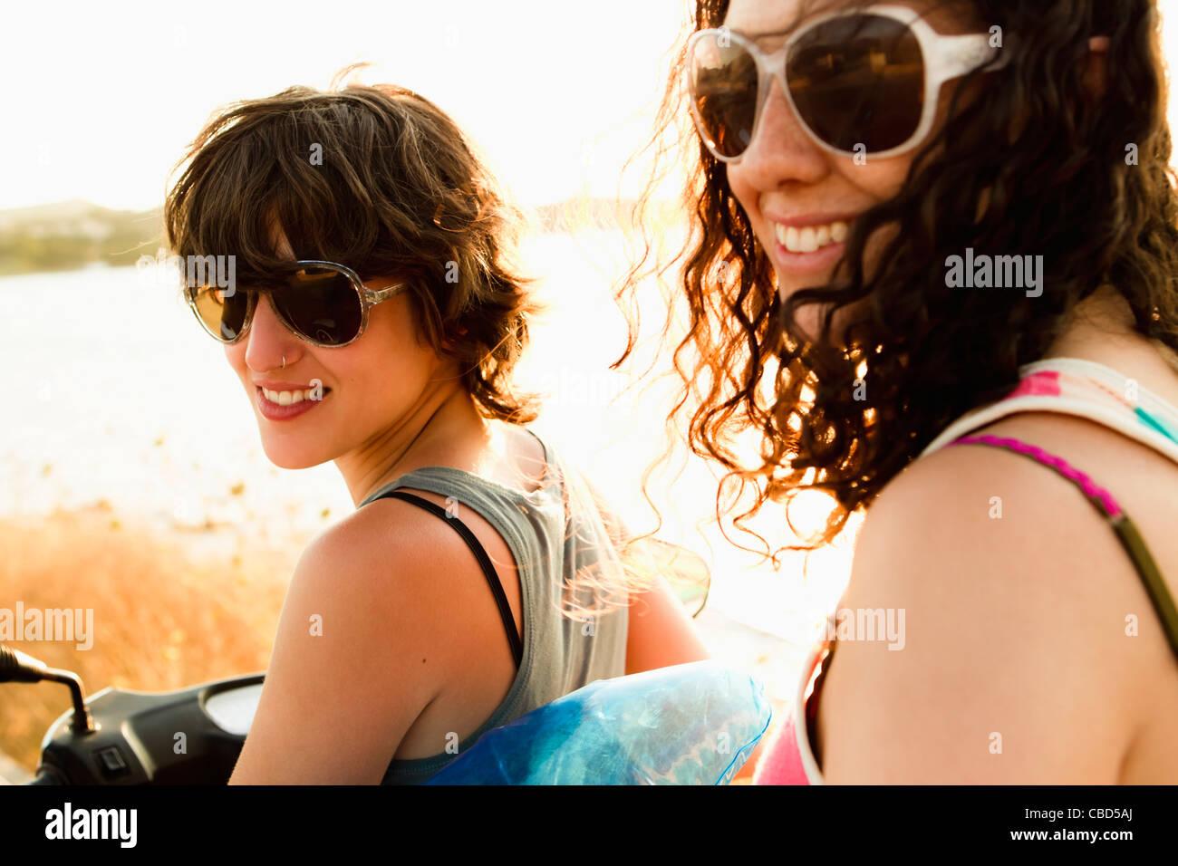 Lächelnde Frauen Motorroller am Strand Stockbild