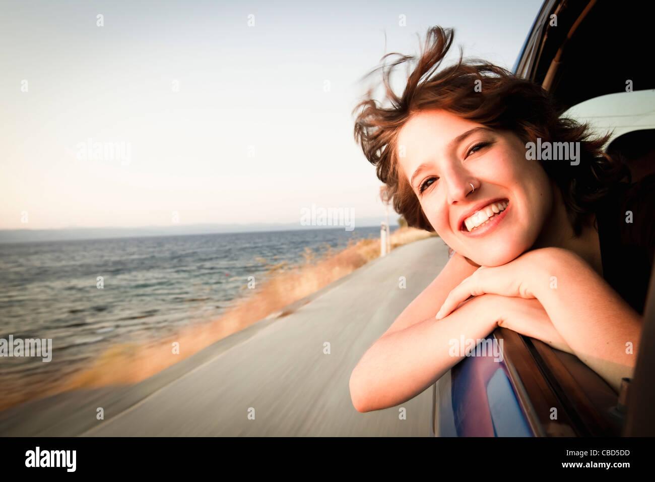 Aus Autofenster lächelnde Frau Stockbild