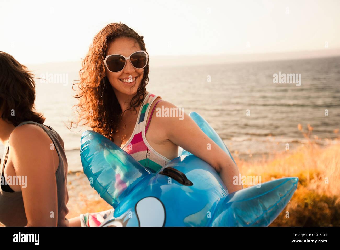 Frau mit aufblasbaren Spielzeug am Strand Stockbild