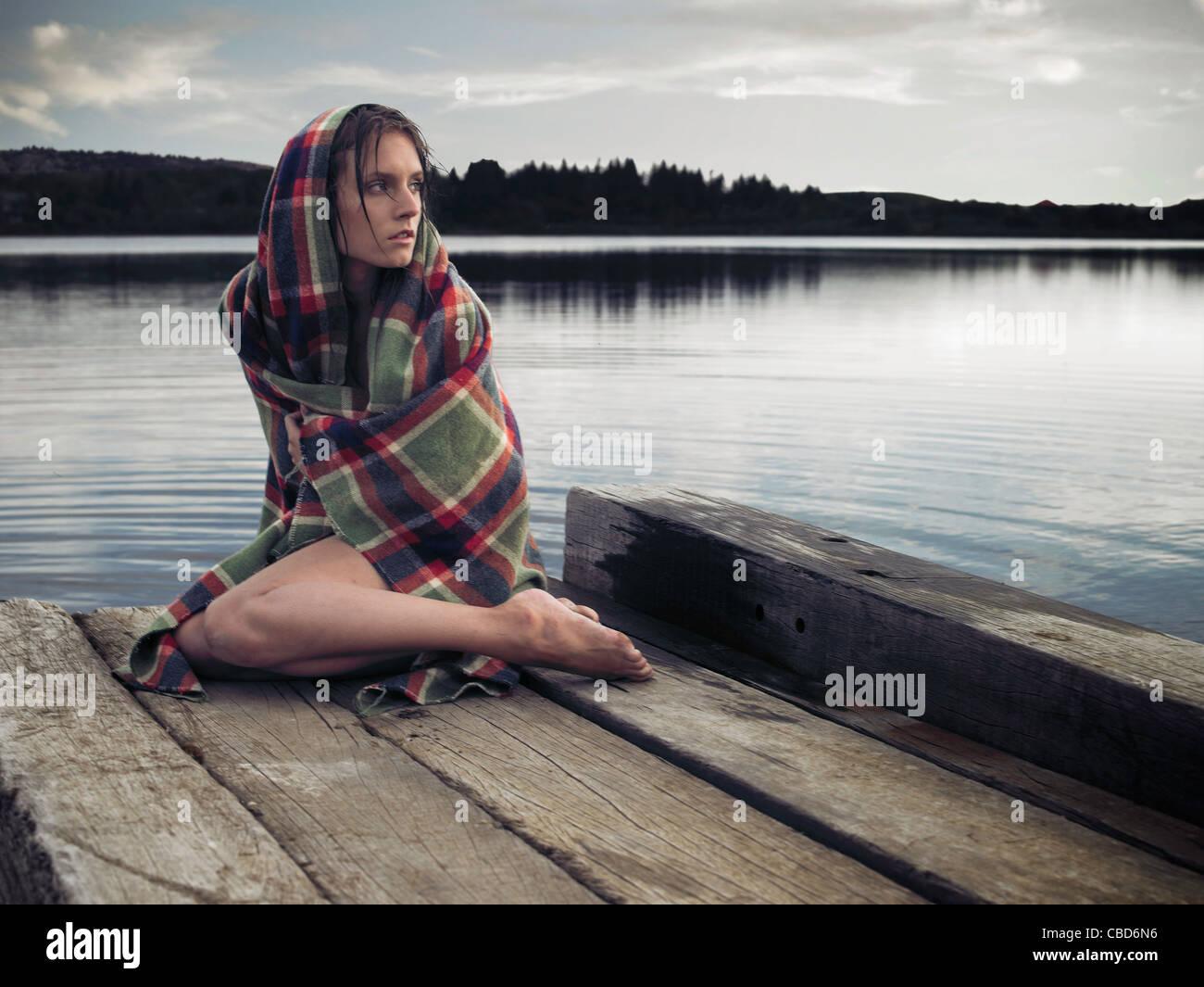 Frau in Decke auf Dock See Stockbild