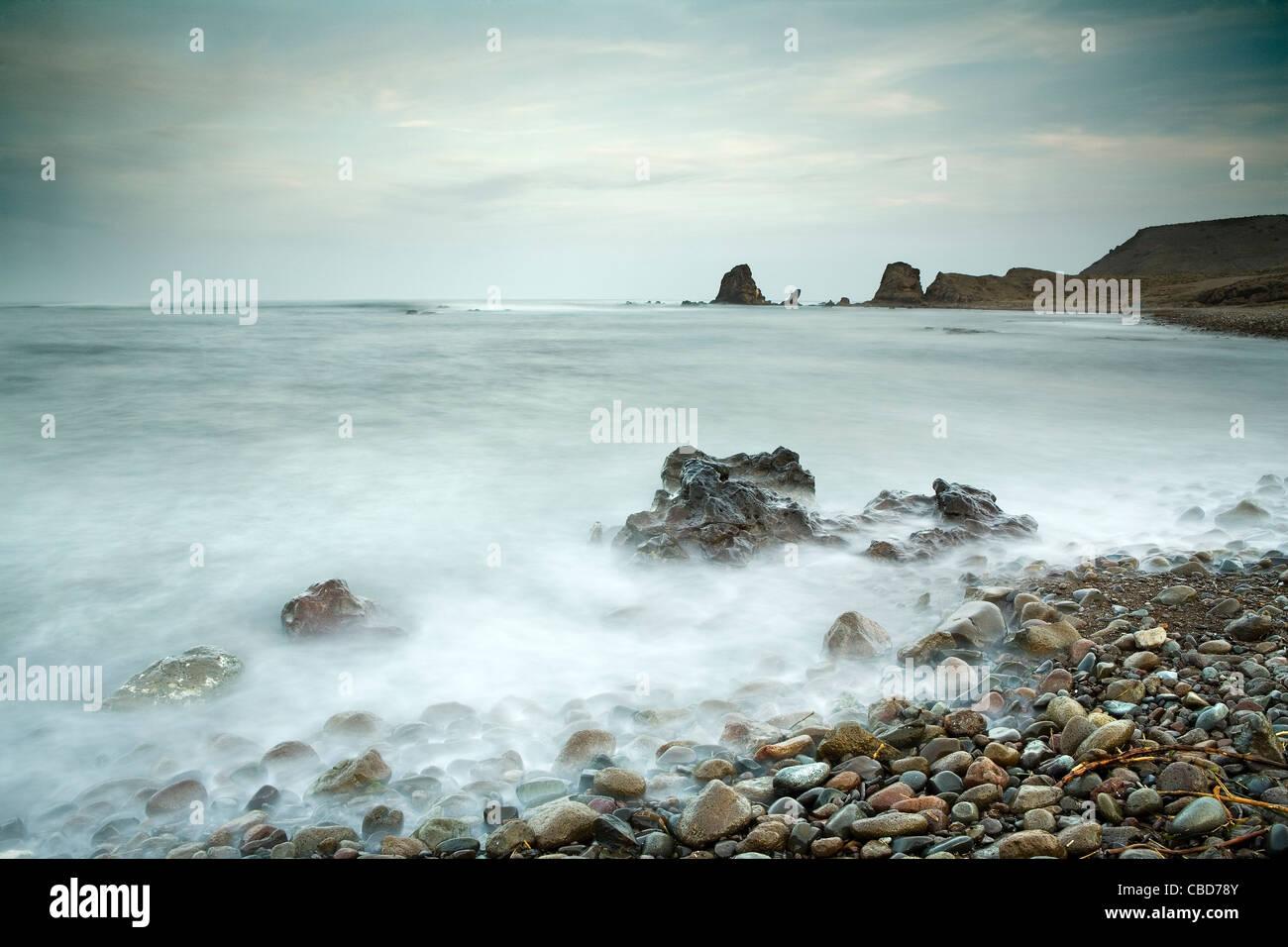 Time-Zeitraffer-Ansicht der Wellen am felsigen Strand Stockbild