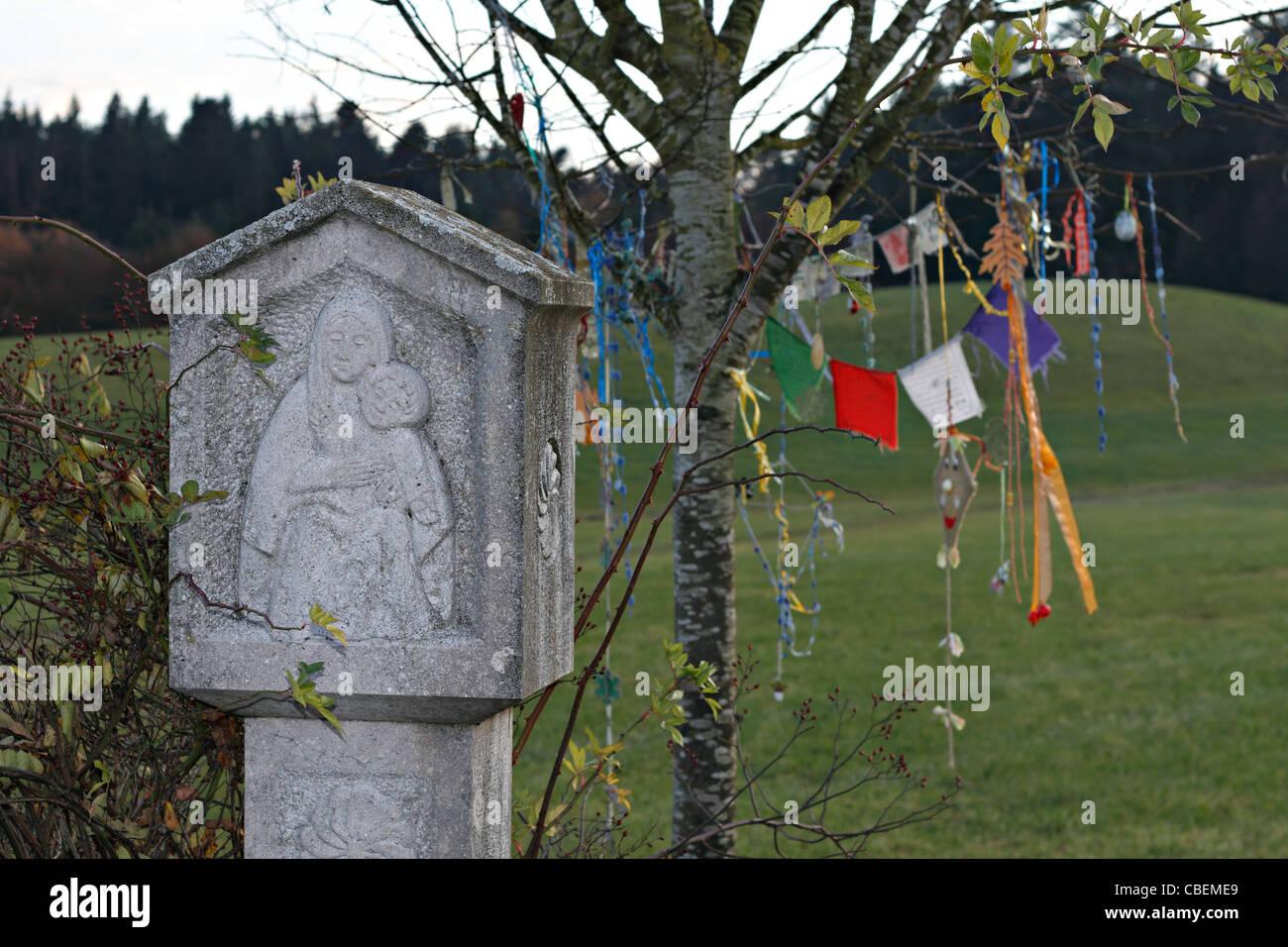 Mary Chistian Bildstock mit buddhistischen Gebet Fahnen hängen von Ästen, obere Bayern Chiemgau Stockbild