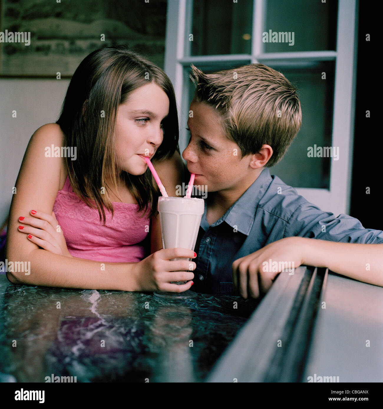 Ein junger Teenager Paar teilen einen Milchshake in einem diner Stockbild