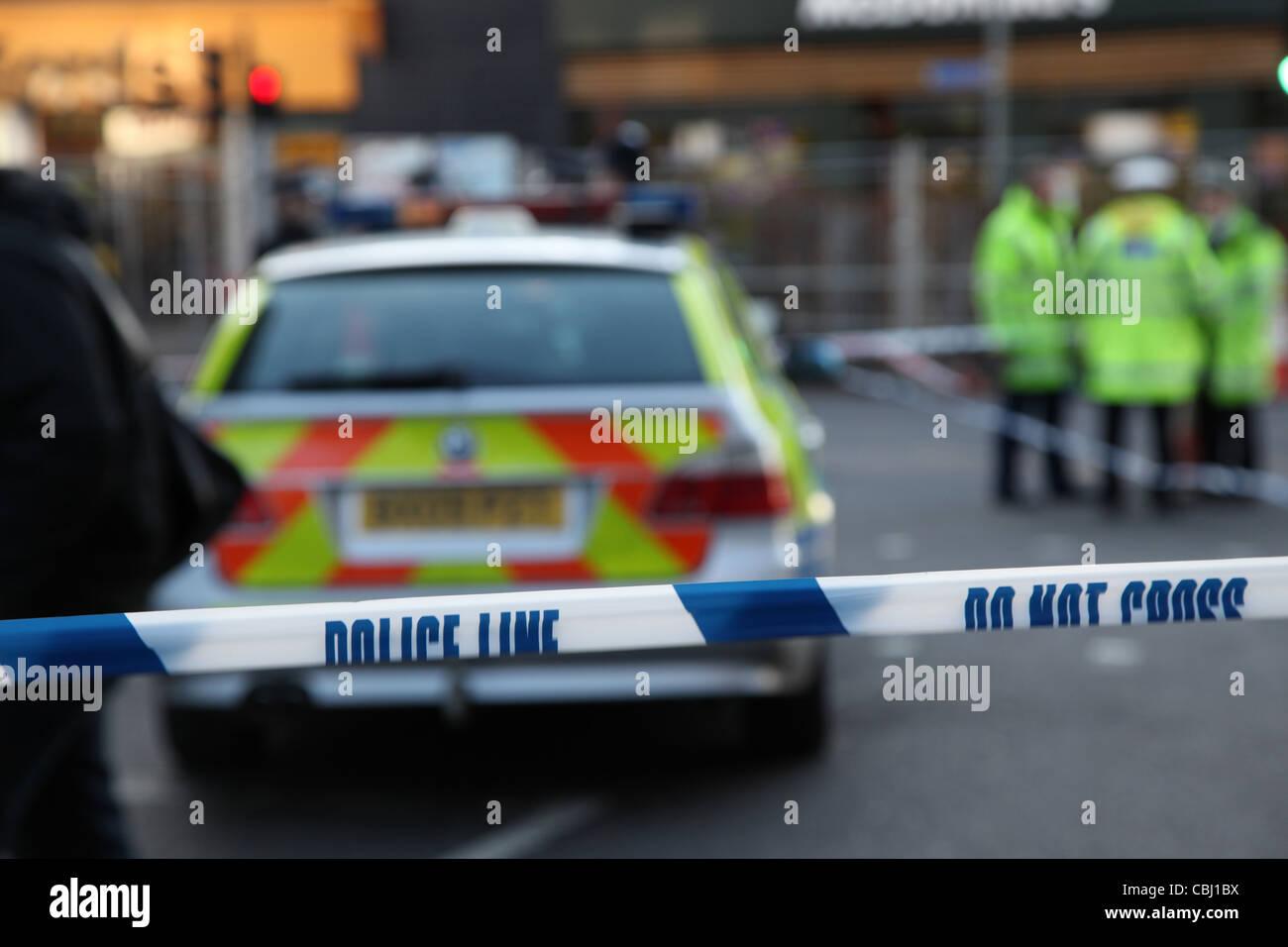 Polizeiabsperrung mit Fahrzeug und Kriminalität Untersuchung-Szene im Hintergrund Stockbild