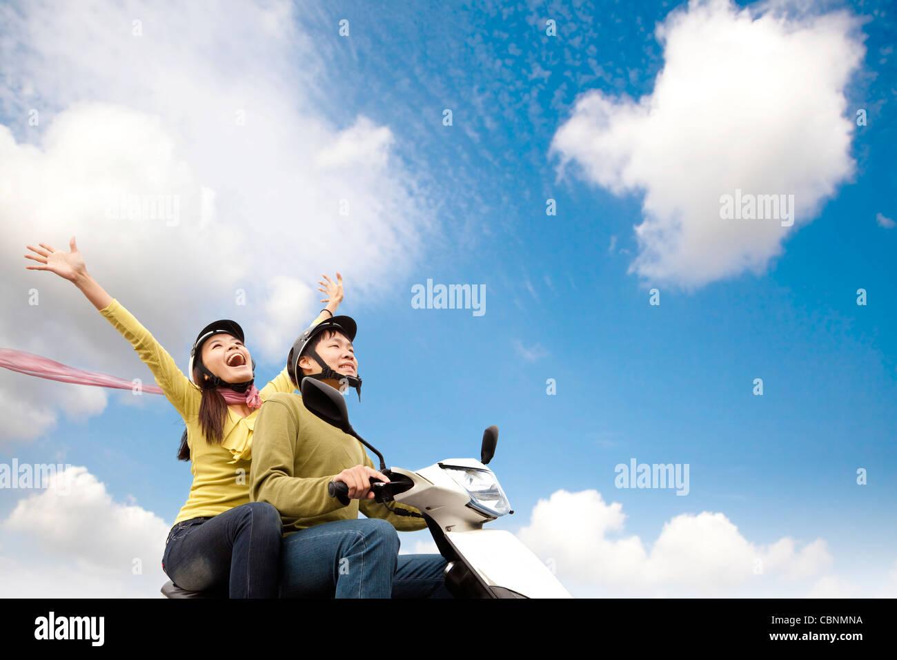 Glückliche junge Paare, die Spaß auf einem Roller Stockbild