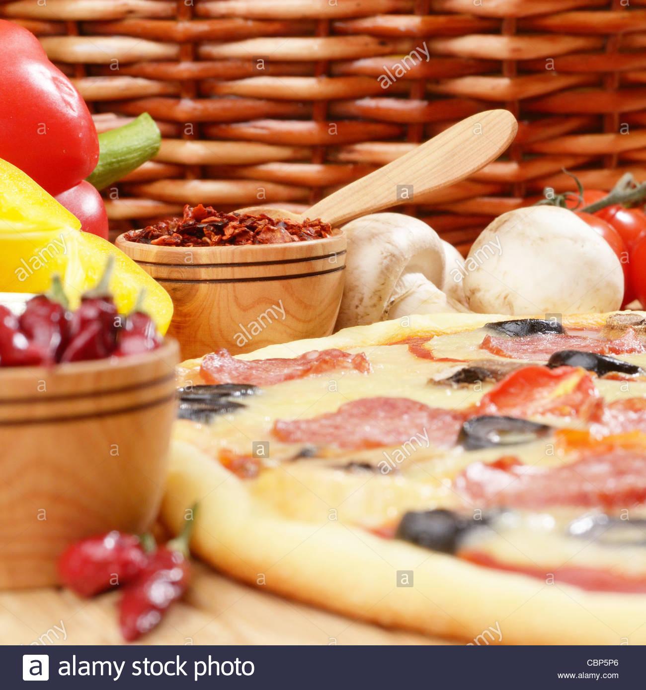 Peperoni-Pizza mit Kirschen und Pilze auf dem Küchentisch Stockfoto ...