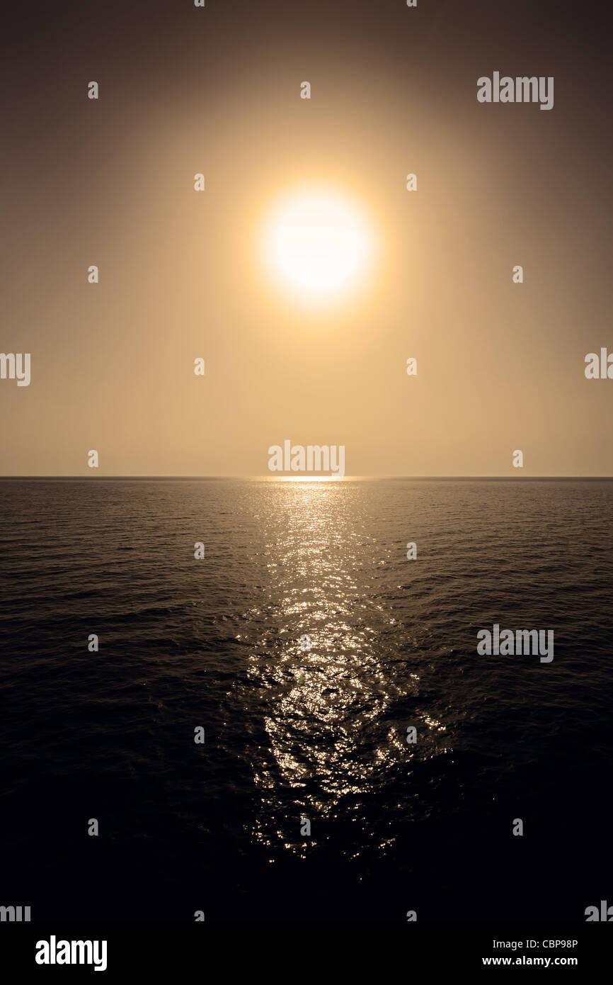 Eine Sonne über dem Meereshorizont. Sepia getönt Bild. Mittelmeer, nahe Insel Santorini, Griechenland. Stockbild