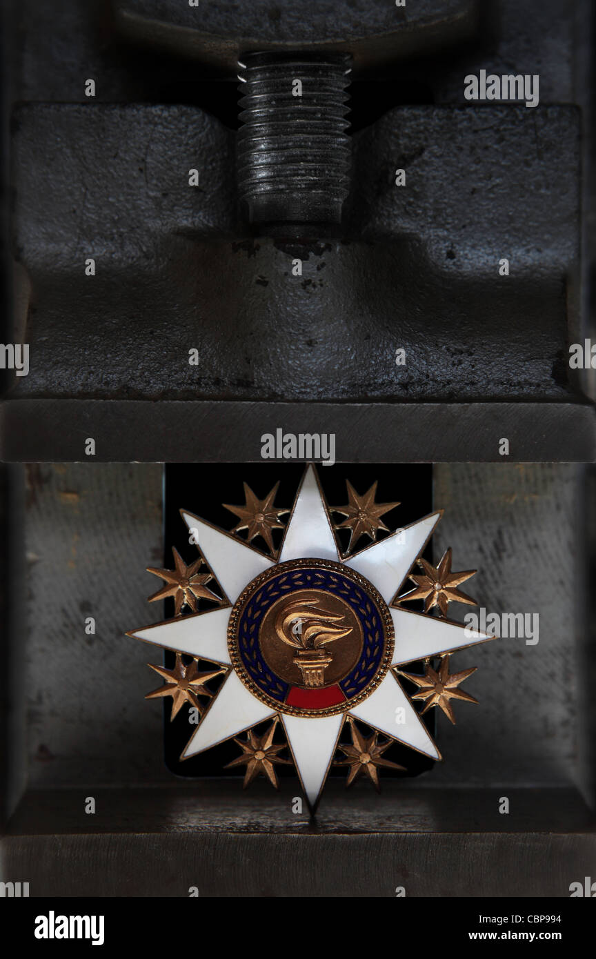 Osten europäischen Kommunistischära Medaille zwischen die Backen einer Presse oder vice Stockfoto
