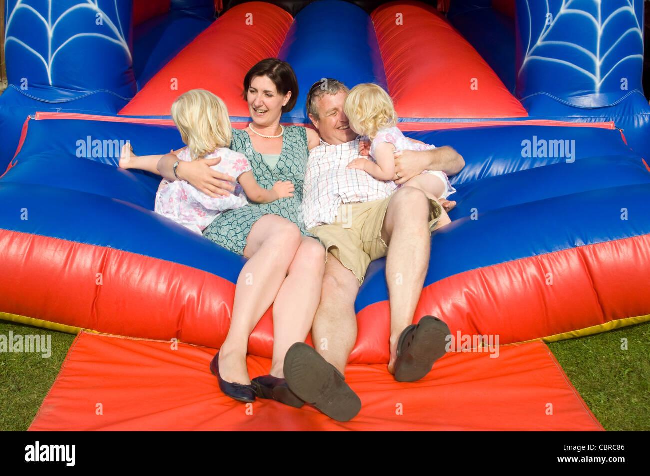 Horizontale informellen Familienfoto mit Mama, Papa und zwei kleine Töchter, die alle spielen auf eine Hüpfburg Stockbild
