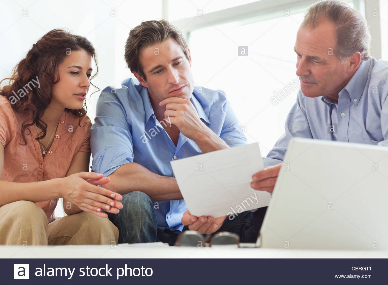 Paar geht über Papierkram mit Finanzberater Stockbild