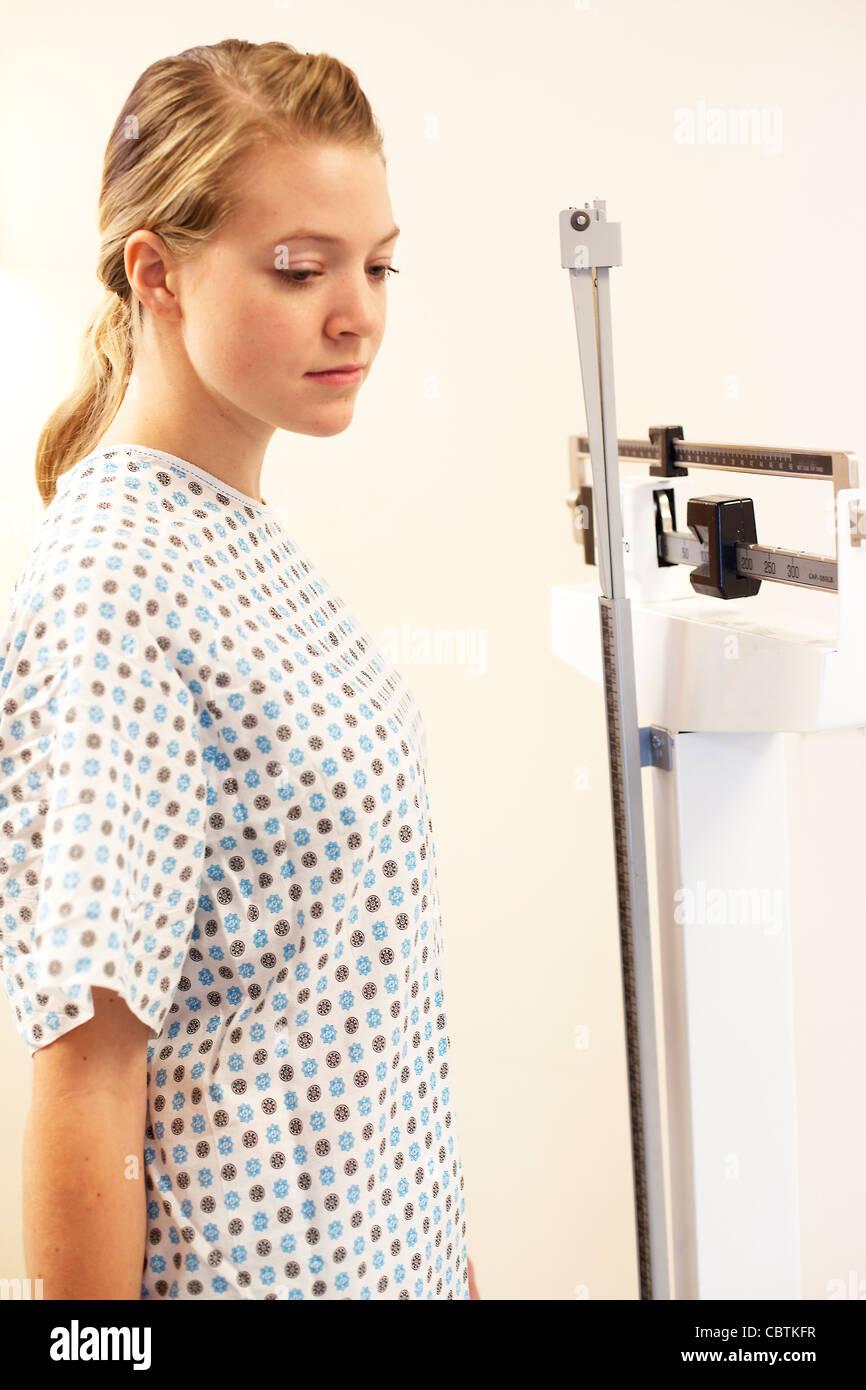 Junge Frau, die Gewichtung selbst Büro Ebene des Arztes. Stockbild