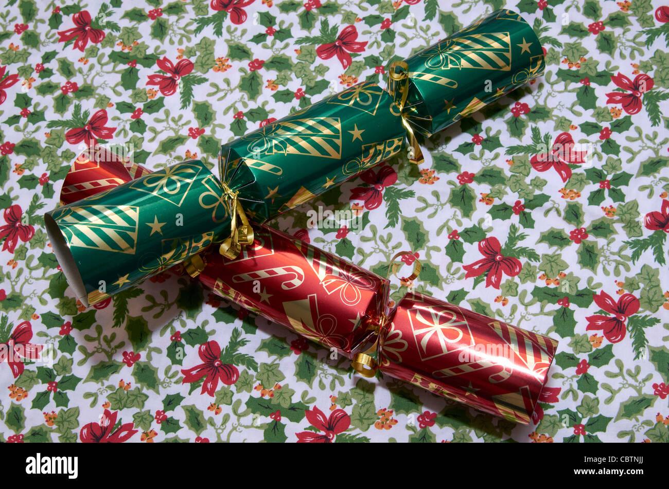 Rote und grüne Christmas Cracker auf einer Tischdecke Weihnachten mit Holly Muster. Stockbild
