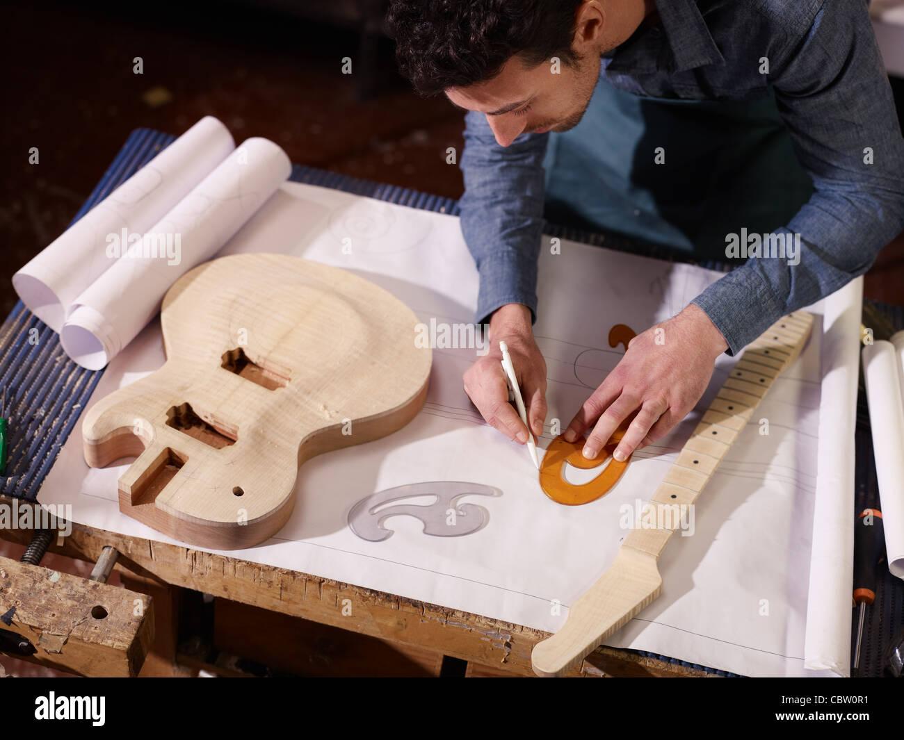 Mitte erwachsener Mann bei der Arbeit als Handwerker in italienischen Werkstatt mit Gitarren und Baupläne Skizzen. Stockbild