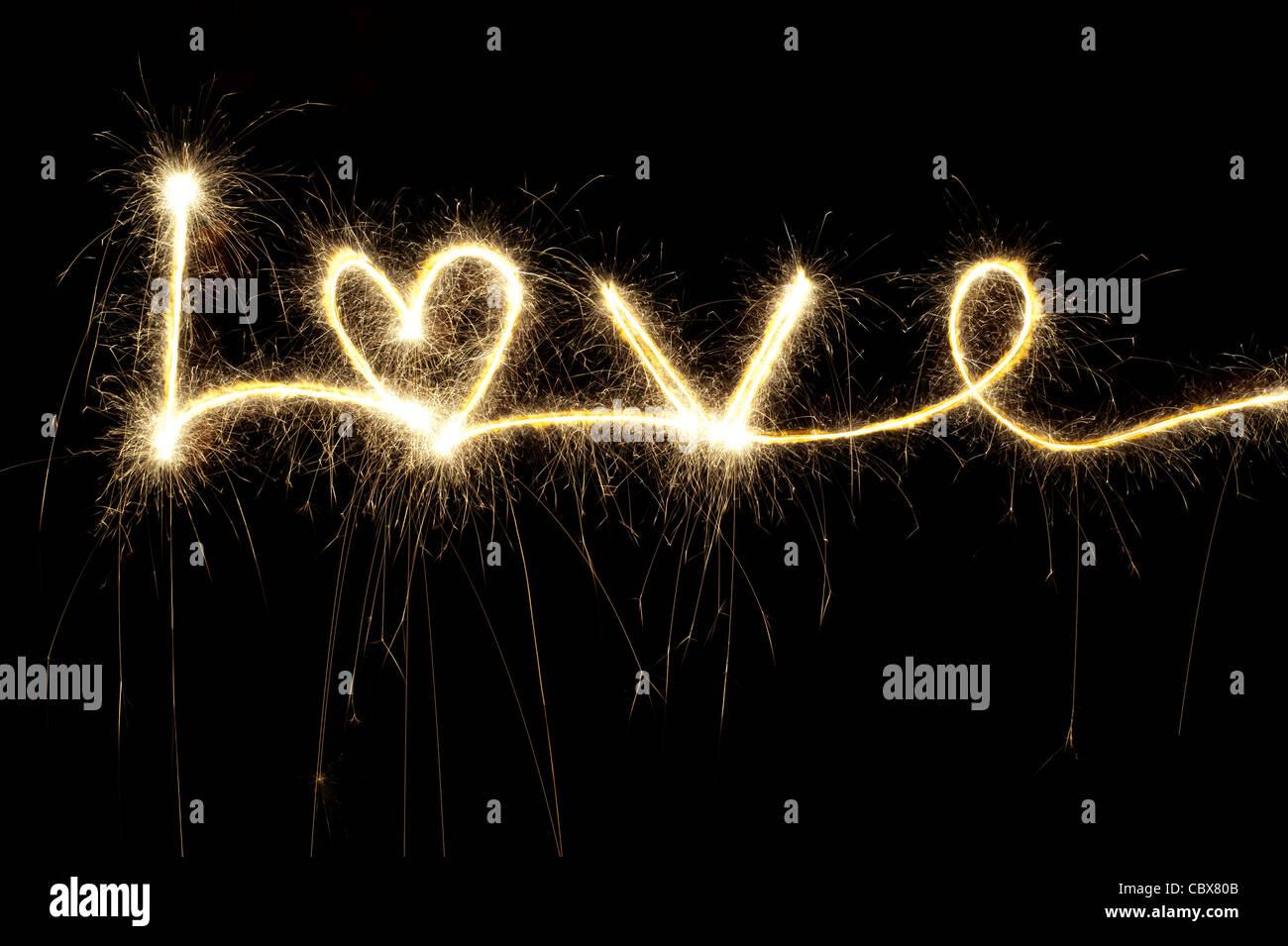 Liebe, geschrieben mit einer Wunderkerze in der Nacht einschließlich einer Herzform Stockbild