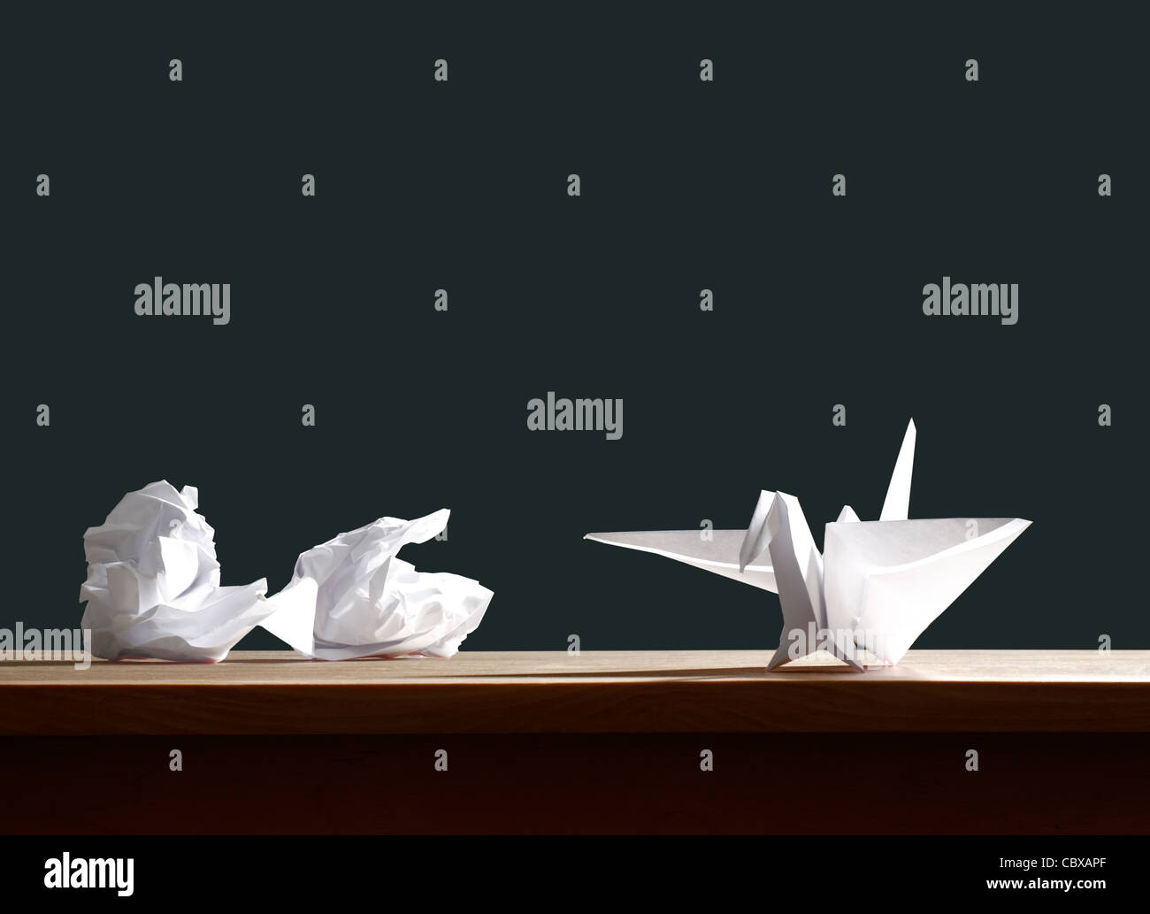 Zerknittertes Papier und Origami Vogel auf Schreibtisch Stockbild