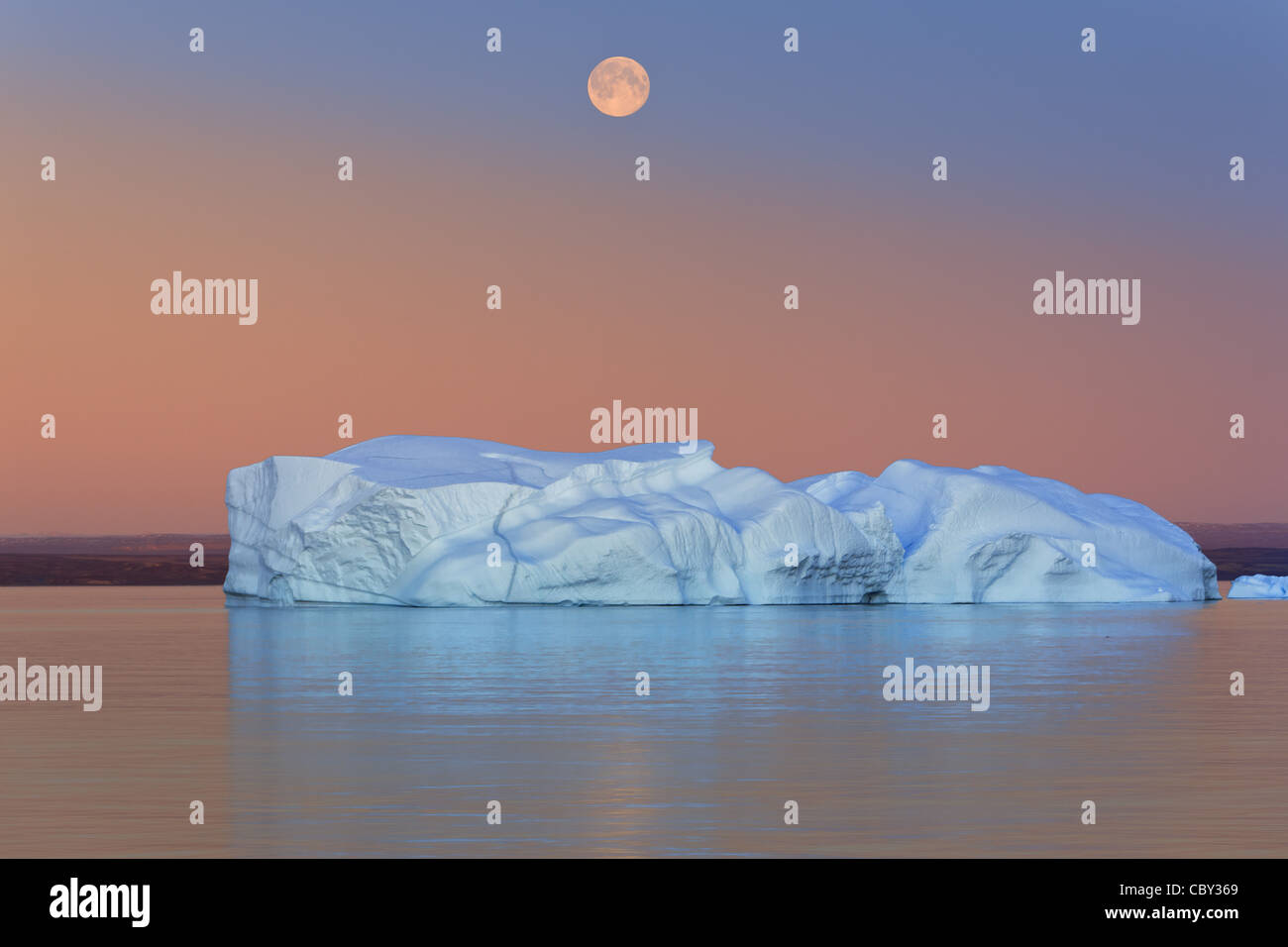 Eisberg bei Sonnenuntergang und Mondaufgang am Hall Bredning, Scoresby Sund, Grönland Stockbild