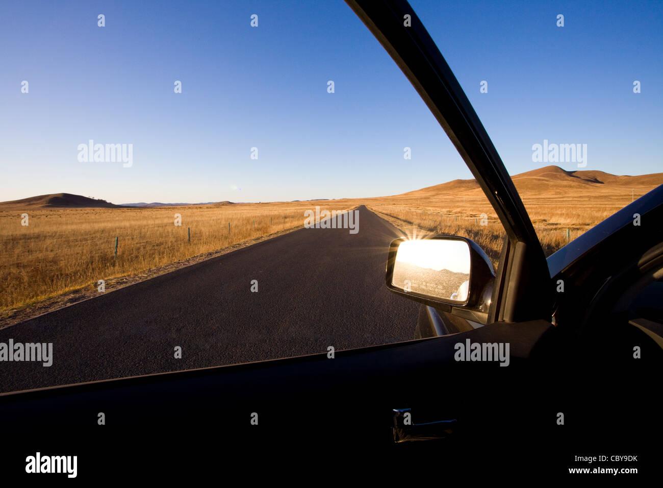 Sideview Autospiegel mit Straße durch Feld im Hintergrund Stockbild