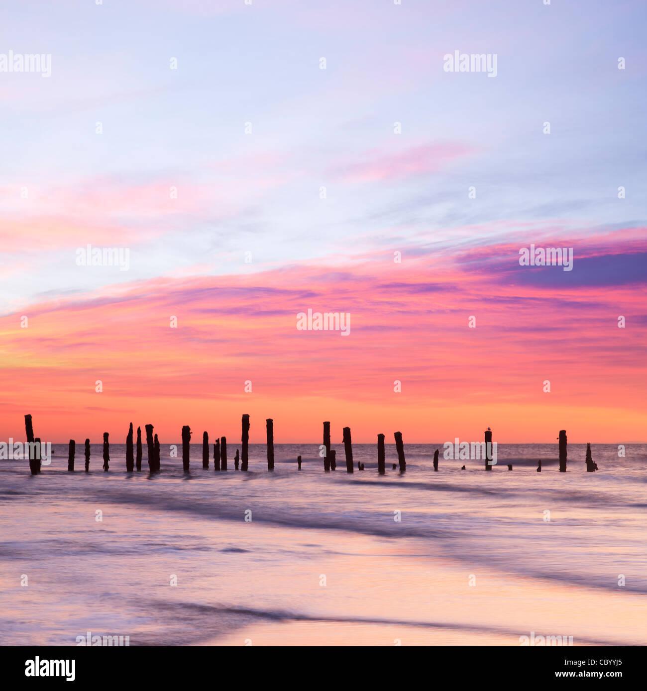 Alten Küstenschutzes in der Morgendämmerung, glatte Wasser aus Langzeitbelichtung. Stockbild