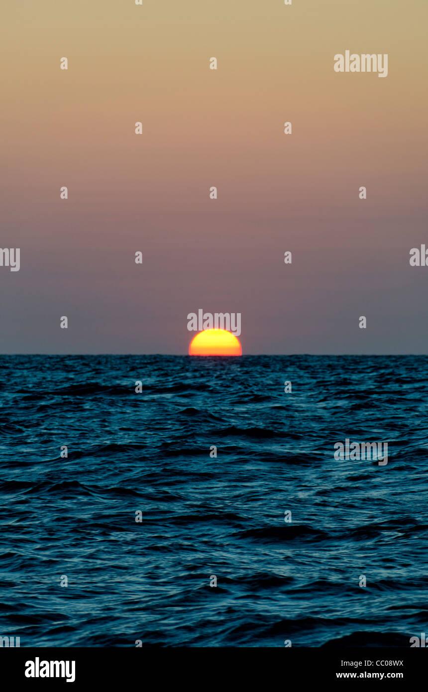 Über die Coral Sea verschwindet die Sonne hinter dem Horizont. Der ...