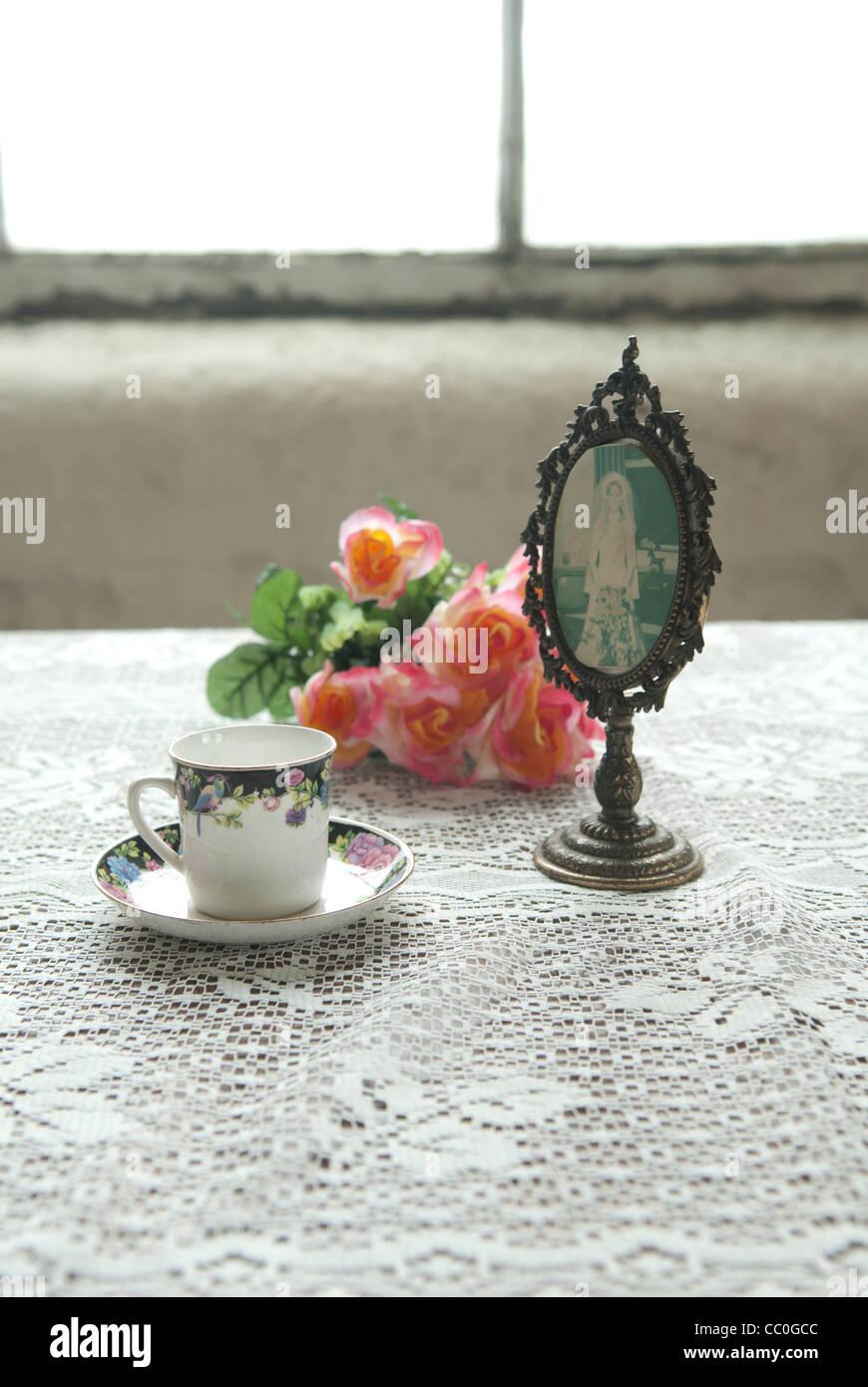 Vintage Teetasse mit Rosen auf einem Tisch am Fenster und ein gerahmtes Bild Stockbild