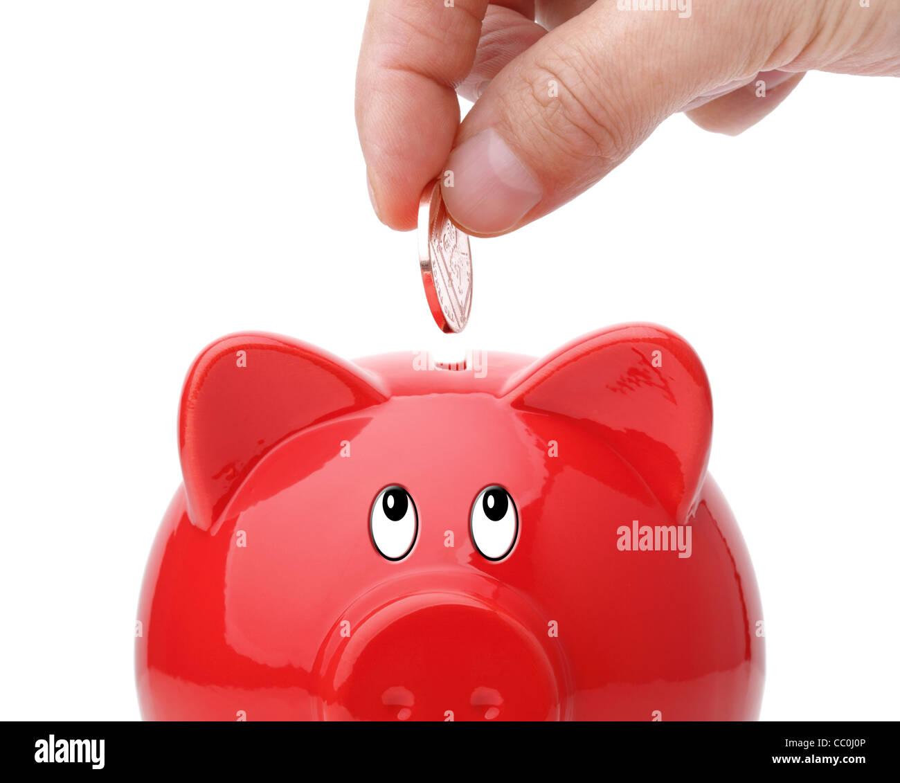 Einfügen von Münze in ein Sparschwein Stockbild
