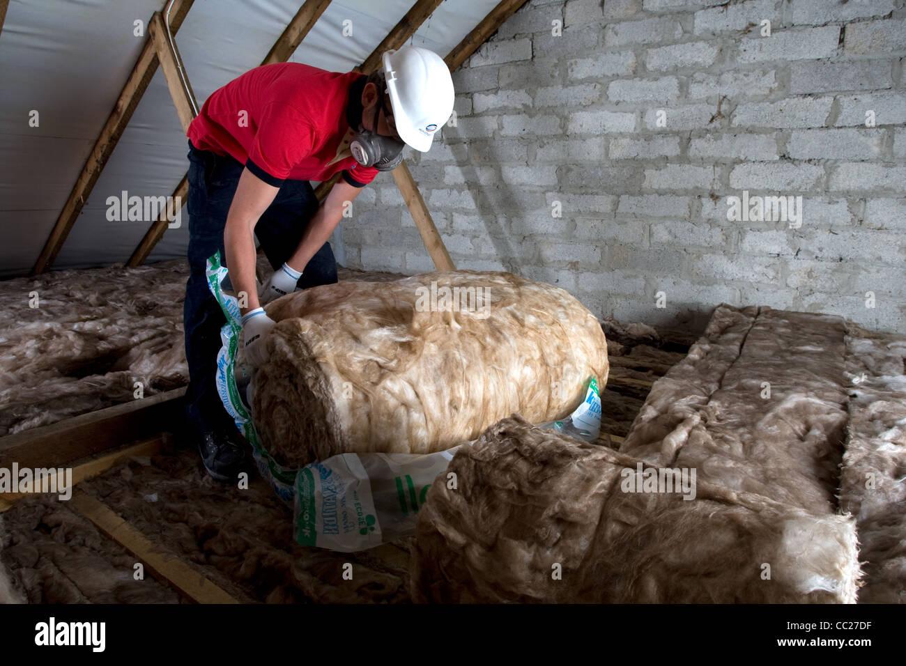 Ein Arbeiter legt Dachdämmung im Dachgeschoss eine Wohnimmobilie Stockbild