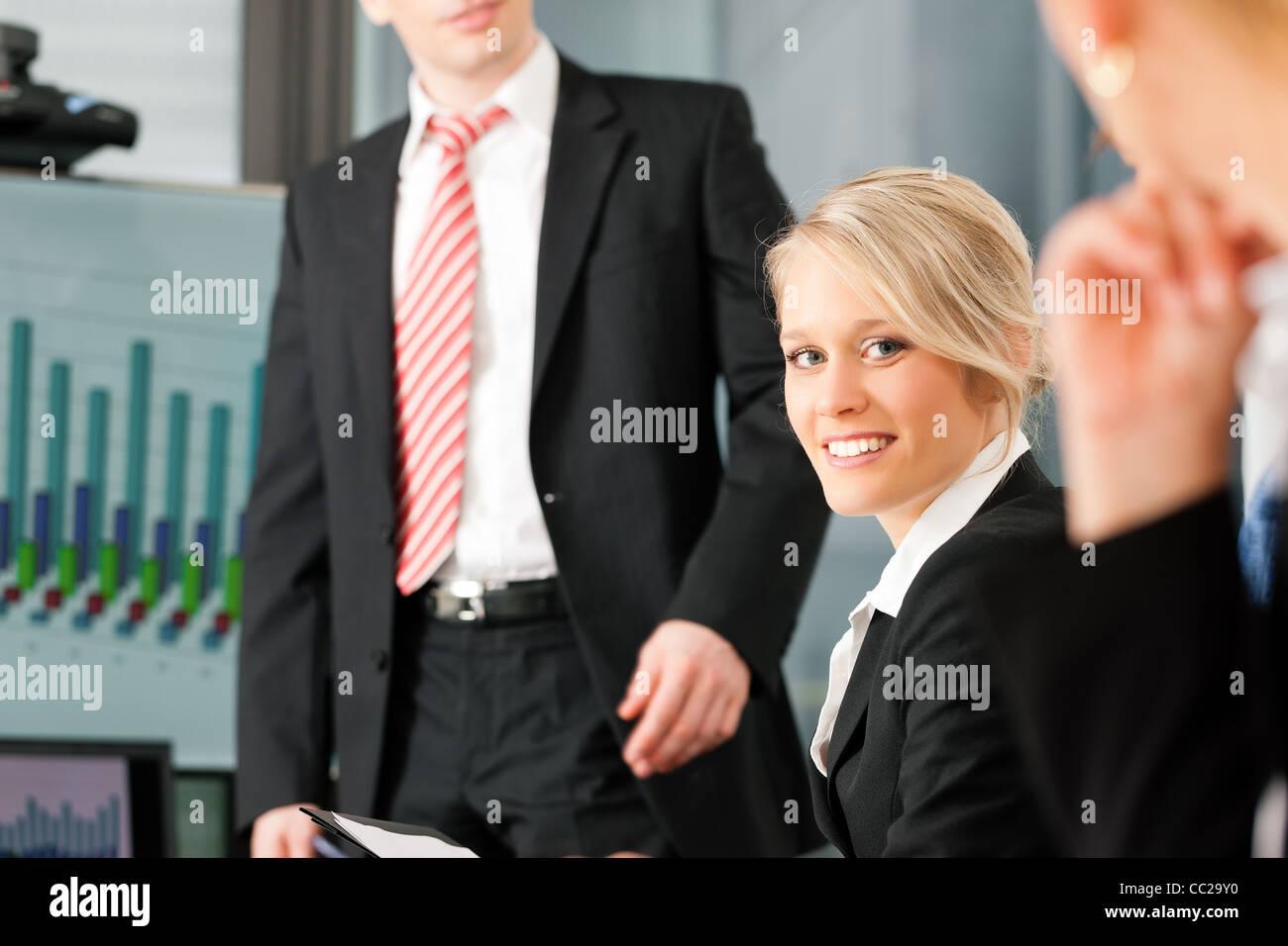 Business - Präsentation im Team; eine weibliche Kollegin steht auf dem Flipchart, eine junge Frau sucht in Stockbild