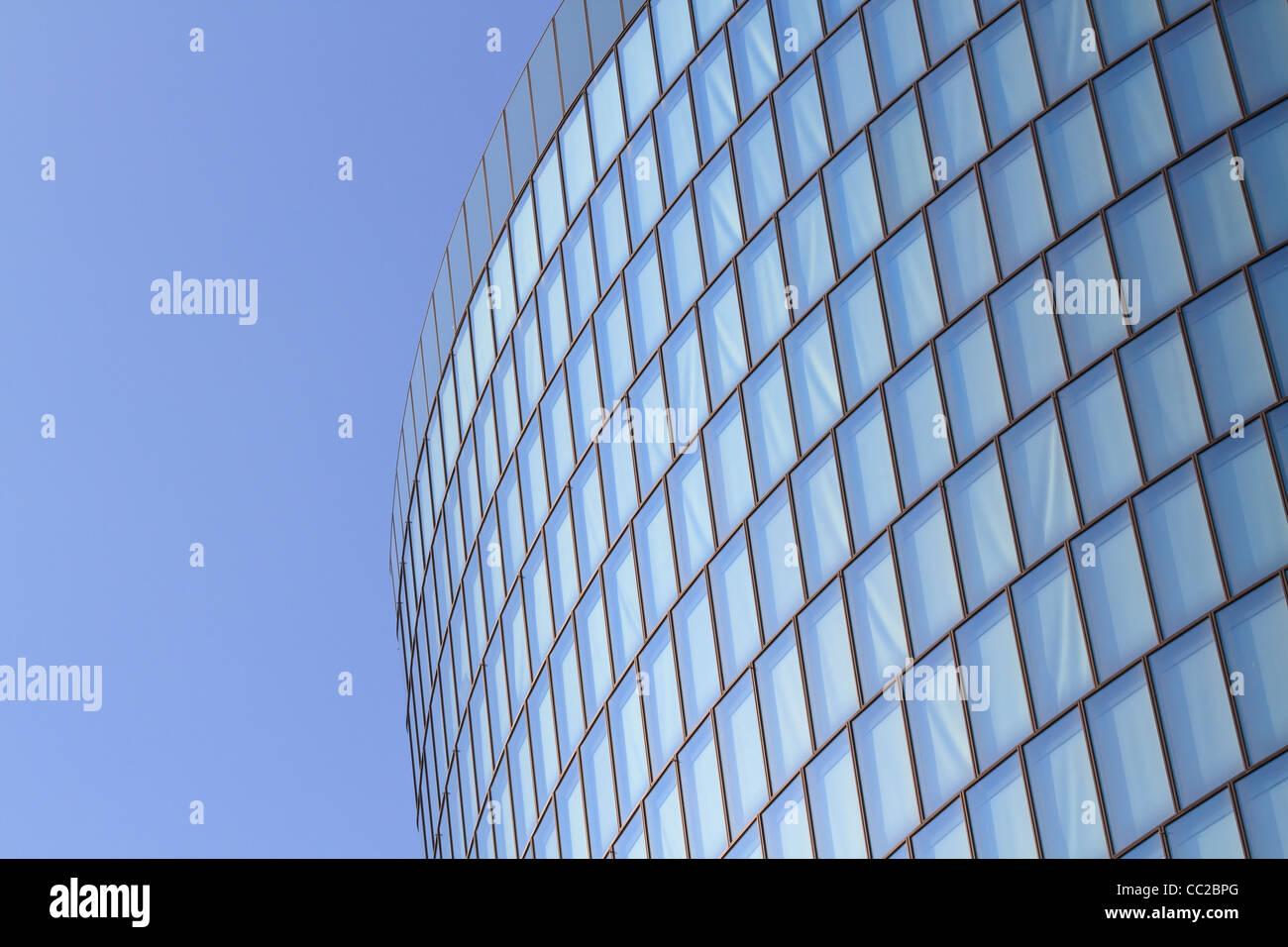 Moderne Glas-Fassade des Büroturms vor blauem Himmel Stockbild