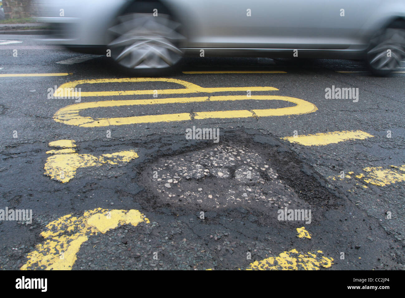 Auto fahren vorbei an Schlagloch Stockbild