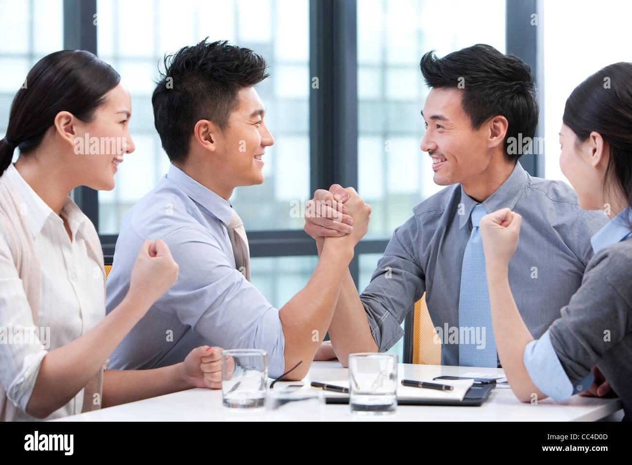 Unternehmer-Armdrücken mit Kollegen jubeln sie auf Stockfoto