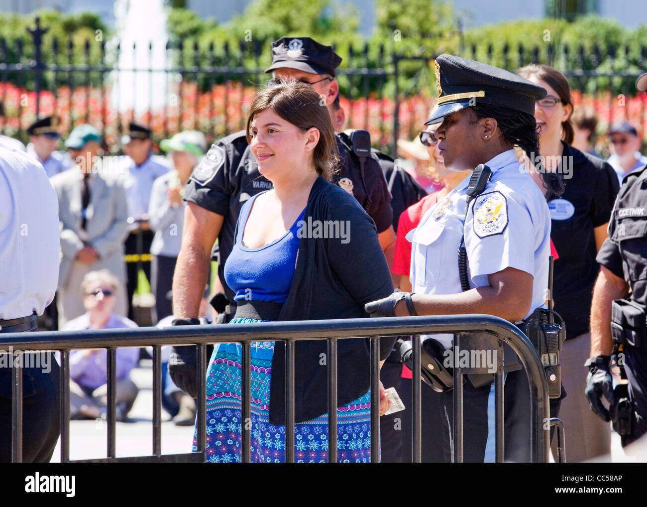 Eine weibliche Demonstrant ist in Handschellen und für vor dem Weißen Haus, Washington, DC, USA protestieren Stockbild
