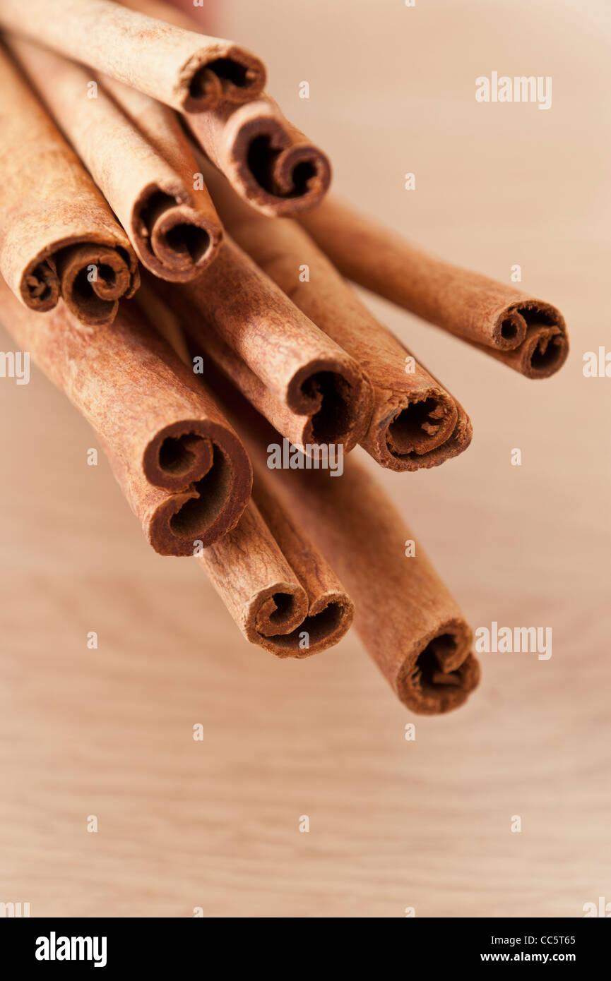 Bündel Zimtstangen gegen einen hellen Holz- Oberfläche Stockbild
