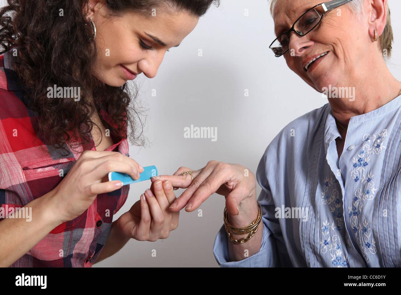 Ältere Frau, die ihre Nägel eingereicht Stockbild