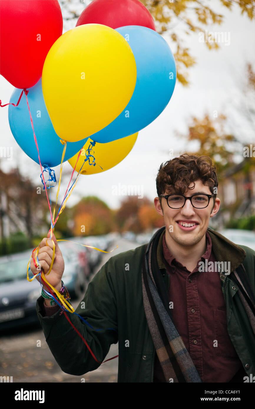 Junger Mann halten bunte Luftballons, Porträt Stockbild