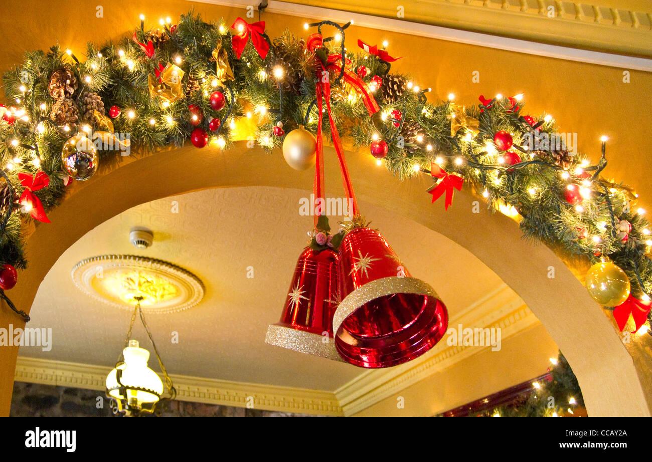 Glocken und Lichterketten als Bestandteil der Weihnachtsschmuck in einem irischen Pub. Stockfoto